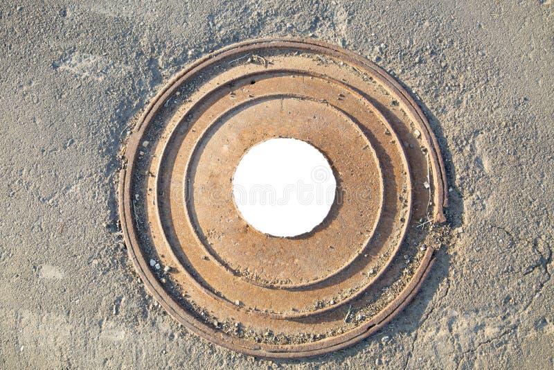 La botola il marrone pesante del ghisa con un modello di parecchi anelli sui precedenti della tirata concreta Nel centro del whi  fotografia stock libera da diritti