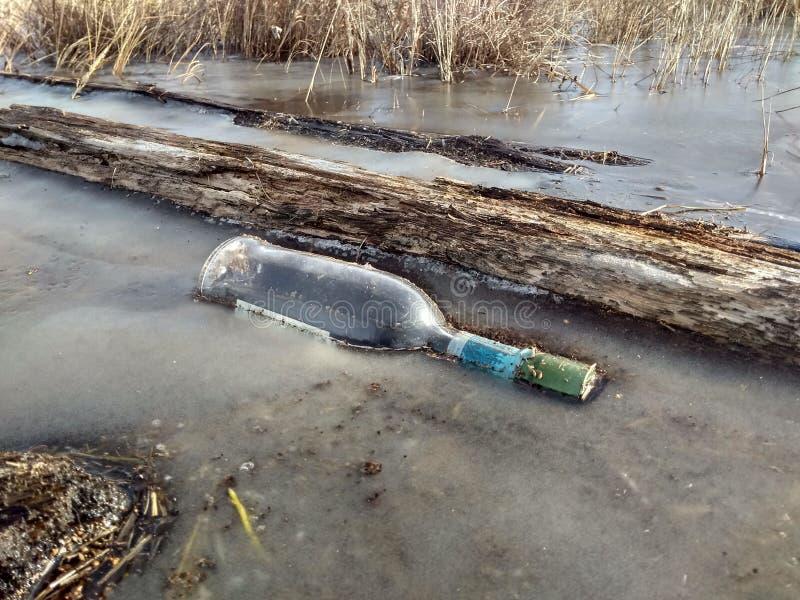 La bottiglia è stata congelata in ghiaccio grigio immagini stock