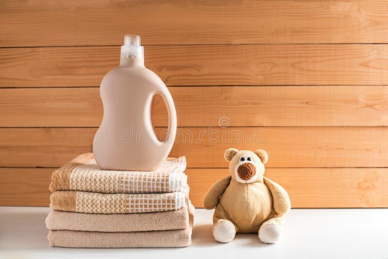 La bottiglia del detersivo vicino ad un mucchio degli asciugamani immagine stock