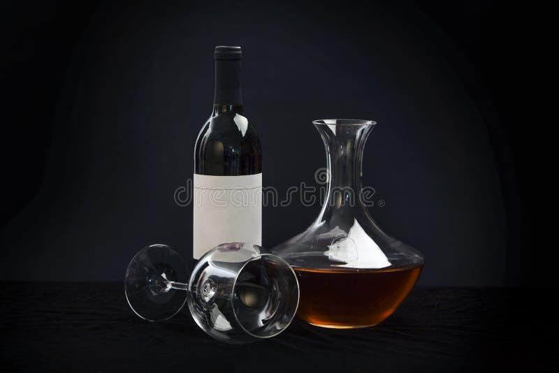 La bottiglia deliziosa ed il vetro del vino rosso hanno riempito di vino su fondo nero fotografia stock libera da diritti