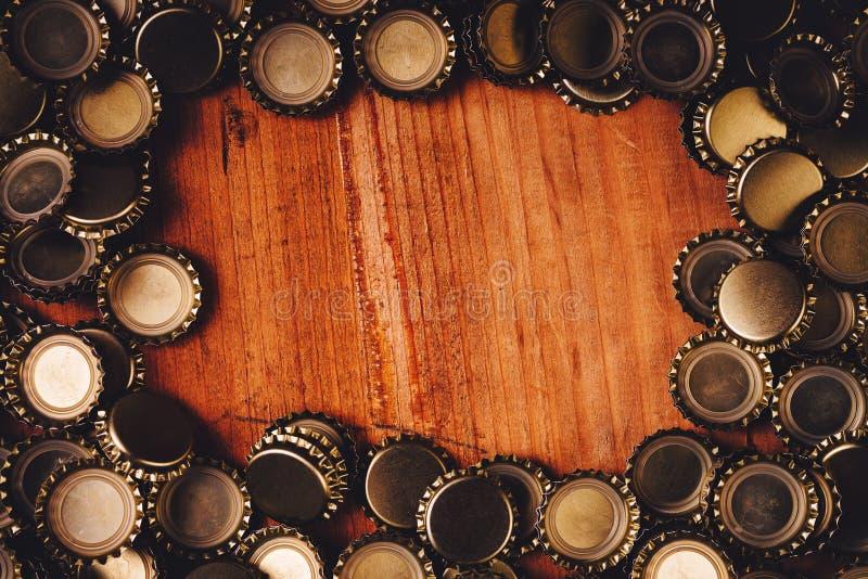 La bottiglia di birra ricopre la struttura sopra fondo di legno immagini stock