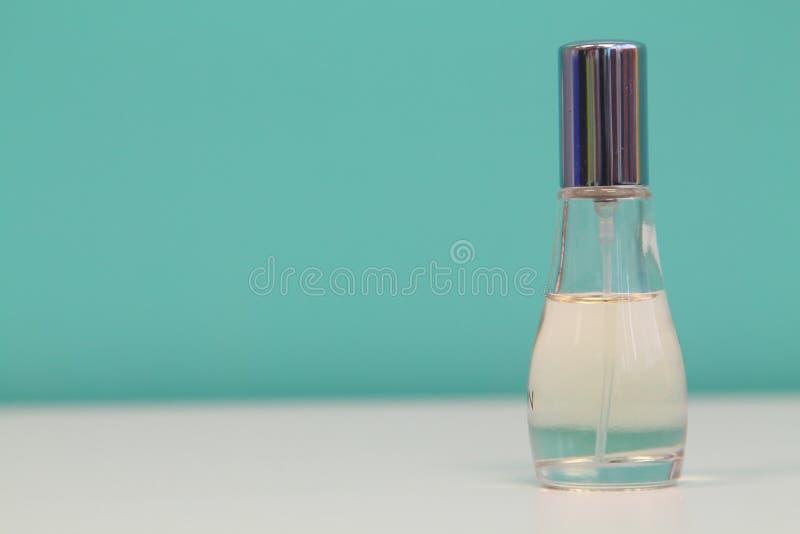 La bottiglia di profumo con la copertura blu-chiaro ha isolato il fondo bianco e blu fotografia stock