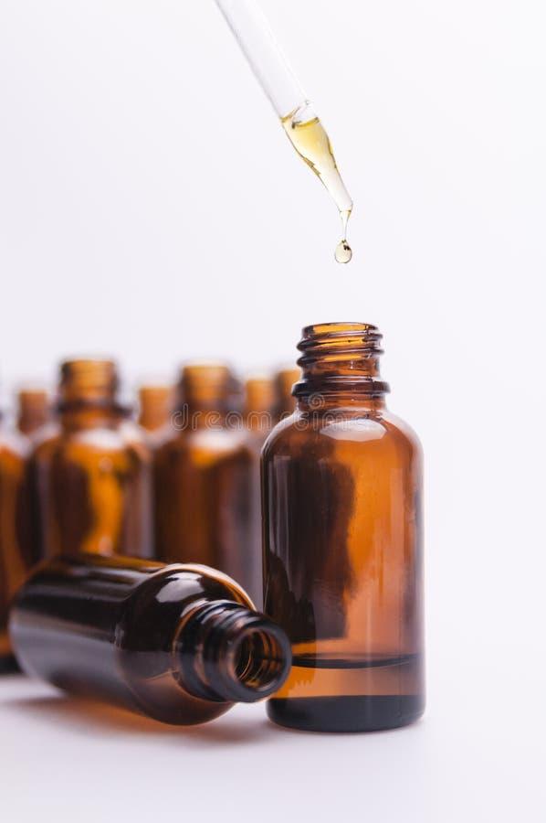 La bottiglia di vetro dell'olio essenziale con il contagoccia e imbottiglia il fondo II immagine stock