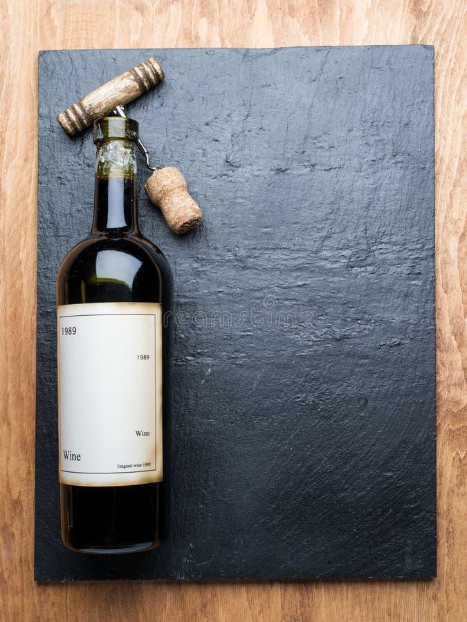La bottiglia di vino e la cavaturaccioli su una grafite imbarcano immagine stock