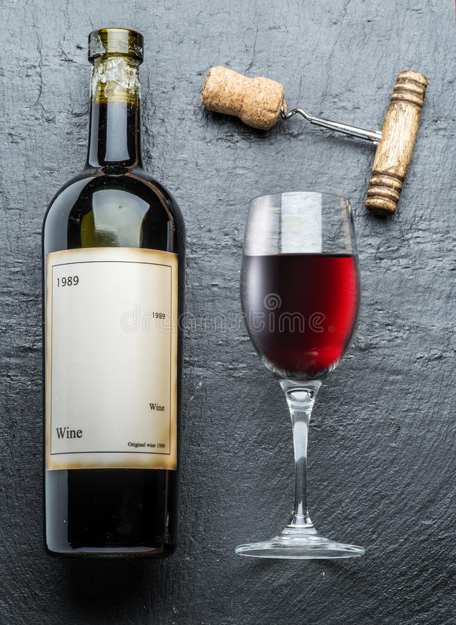 La bottiglia di vino, il vetro di vino e la cavaturaccioli su una grafite imbarcano immagini stock libere da diritti