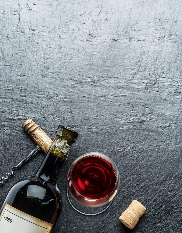 La bottiglia di vino, il vetro di vino e la cavaturaccioli su una grafite imbarcano fotografia stock