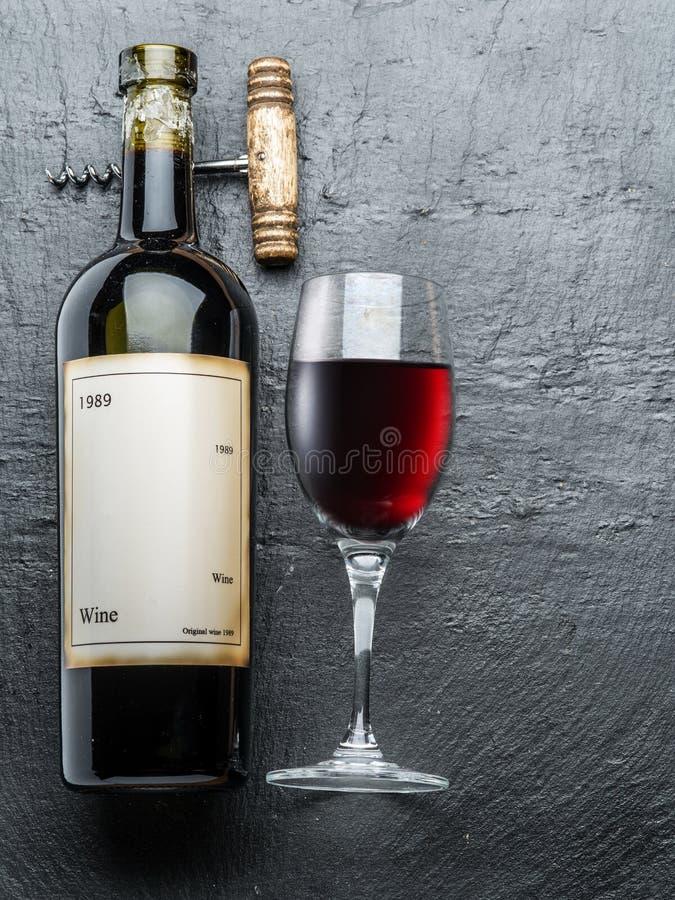 La bottiglia di vino, il vetro di vino e la cavaturaccioli su una grafite imbarcano fotografie stock