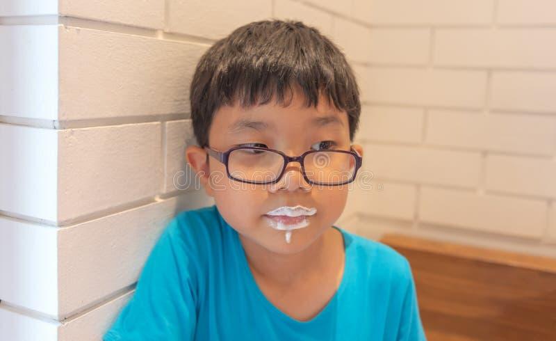 la bouche écumeuse de lait de boissons de garçon est désordonnée image stock