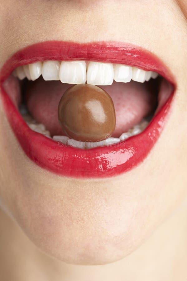La bouche du femme mordant sur le chocolat photographie stock libre de droits