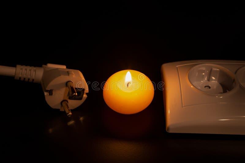 La bougie jaune brûlante, la prise blanche de contact et la prise blanche sont dans l'obscurité sur la table/fond noirs Jour inte images libres de droits