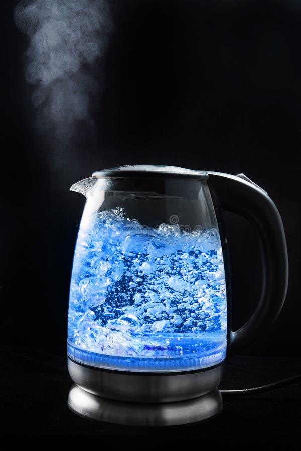 La bouilloire en verre de ébullition avec la lumière bleue sur un fond noir, vapeur vient du bec image stock