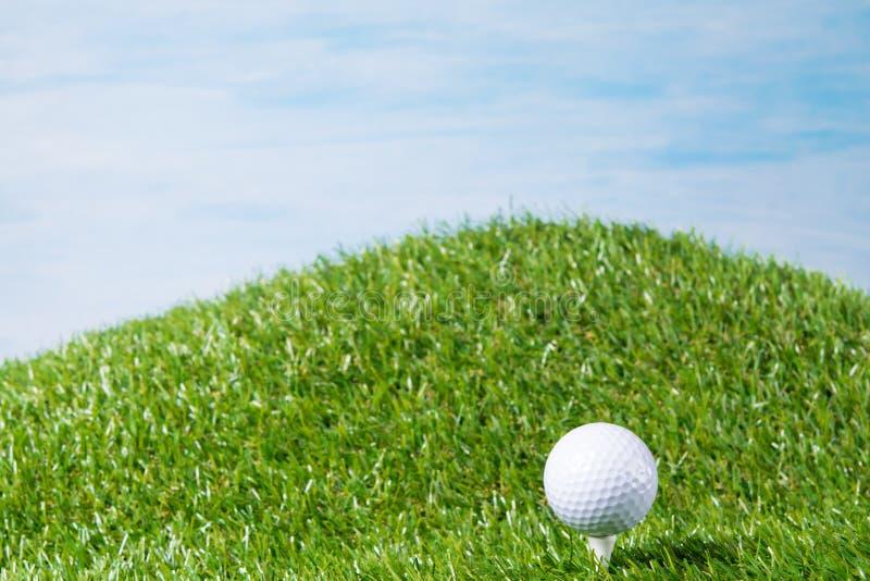 La boule blanche se trouve sur une cheville coincée dans une pelouse pour un jeu du golf, sur un fond de ciel bleu photographie stock libre de droits