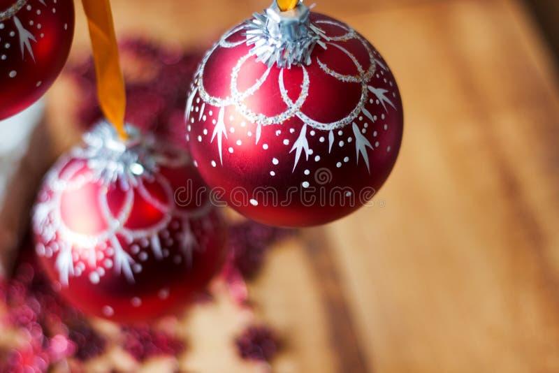 La boule de Noël ornemente la décoration accrochant sur la branche d'arbre de sapin au-dessus du fond de lumières rouges photo stock