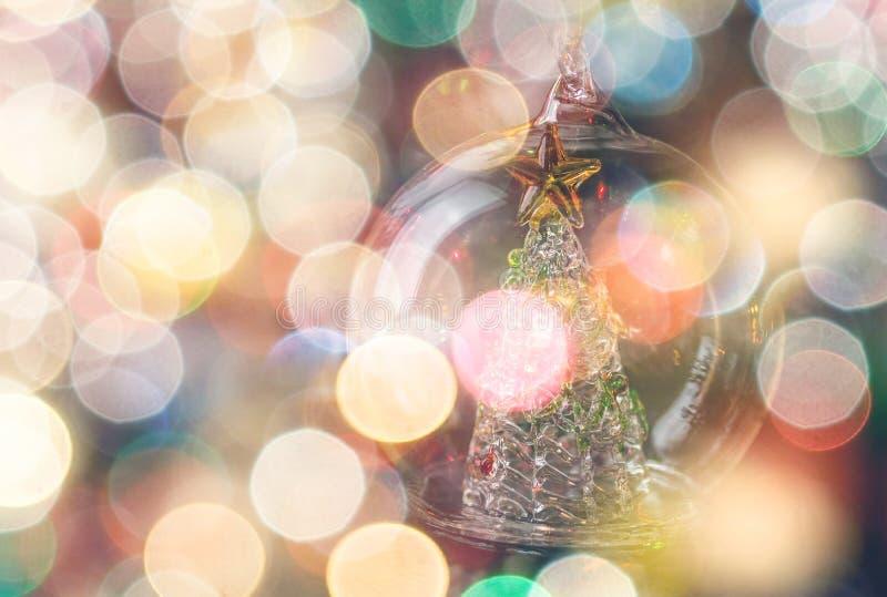 La boule en verre avec l'arbre de Noël entouré par le bokeh s'allume photos stock