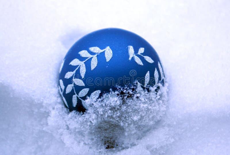 La boule en verre bleue de Noël dans la neige photo libre de droits
