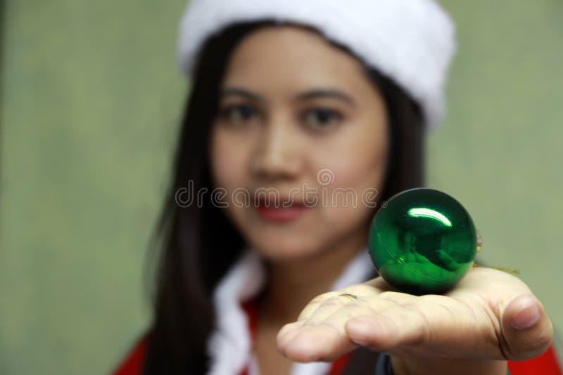 La boule magique verte sur la main de focalisent l'Asiatique Santa Girl Dress image libre de droits