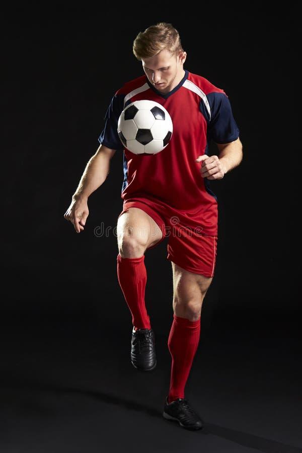 La boule roulante de footballeur professionnel dans le studio image stock