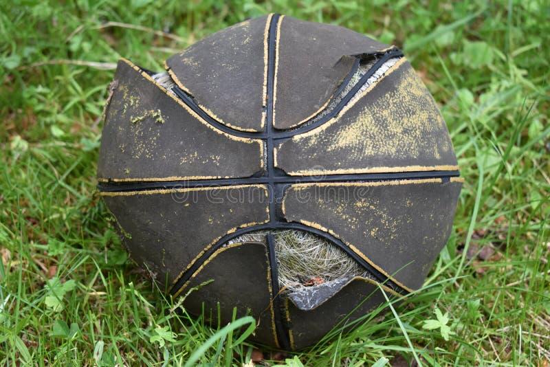 La boule usée et dégonflée de basket-ball dans l'herbe image stock