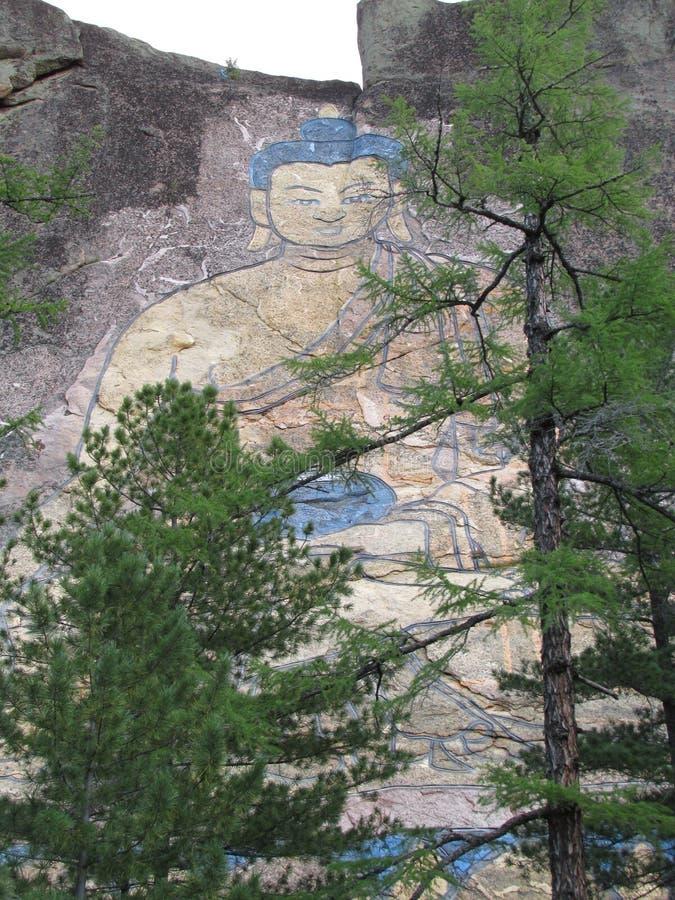 La Bouriatie l'image 30-meter de Bouddha a découpé sur une roche photo stock