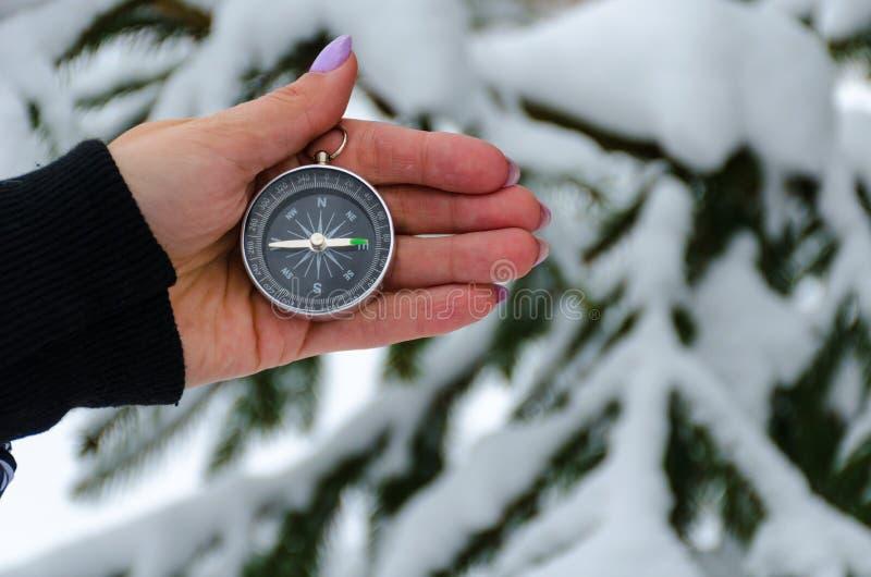 La boussole dans les mains pendant le voyage d'hiver photographie stock