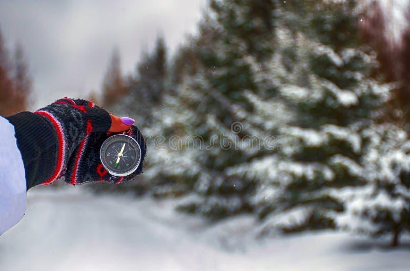 La boussole dans les mains pendant le voyage d'hiver images stock