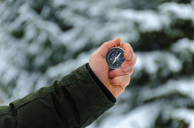 La boussole dans les mains pendant le voyage d'hiver photos libres de droits