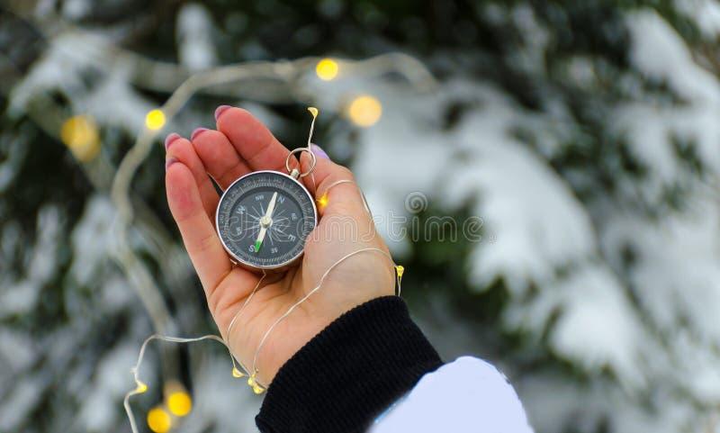 La boussole dans les mains pendant le voyage d'hiver image stock