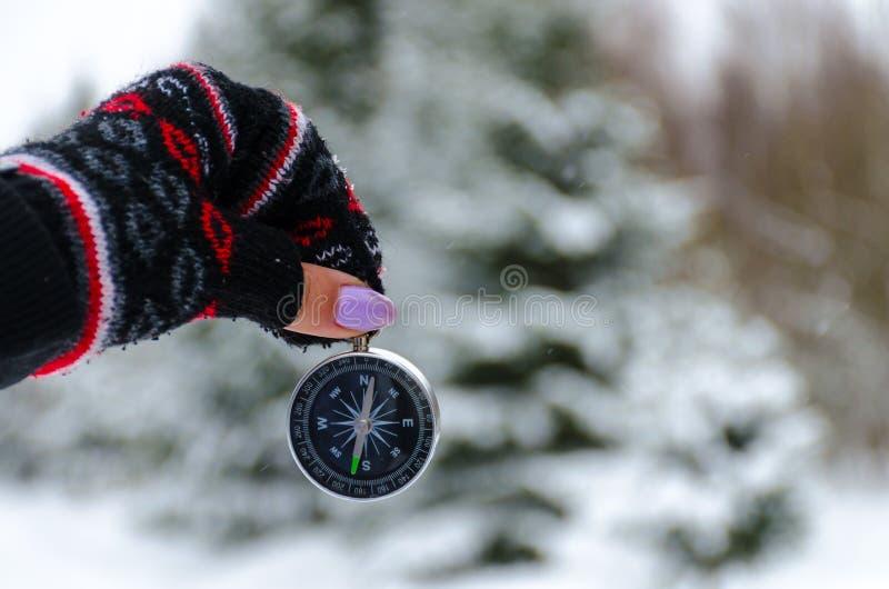 La boussole dans les mains pendant le voyage d'hiver photographie stock libre de droits