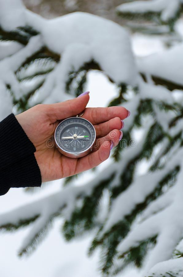 La boussole dans les mains pendant le voyage d'hiver photo stock