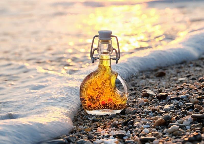 La bouteille d'huile d'olive grecque sur la plage pierreuse de mer dans la vague mousseuse de mer photo stock