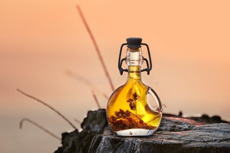 La bouteille d'huile d'olive grecque sur le fond de coucher du soleil de nature photos stock