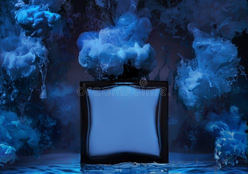 La bouteille de parfum du ` s de l'homme dans une vague d'eau avec des clubs de peinture bleue autour de la bouteille photographie stock