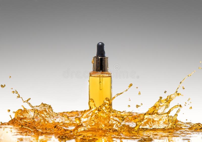 La bouteille du cosmétique jaune dans la grande éclaboussure d'huile sur le fond de gris de gradient photographie stock