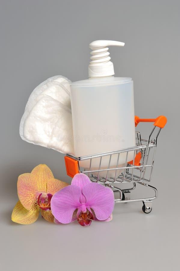 La bouteille en plastique de gel de pompe intime de distributeur, serviette sanitaire dans le chariot avec l'orchidée fleurit image stock