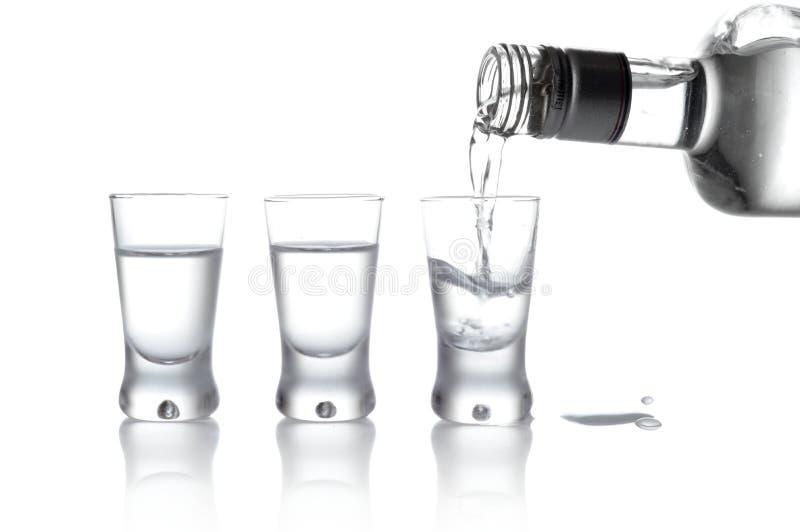 La bouteille et les verres de vodka ont versé dans un verre d'isolement sur le petit morceau photos libres de droits