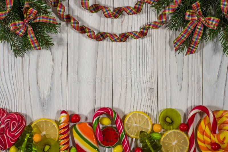 La branche du sapin avec les sucreries colorées sur un tabl en bois blanc photos stock