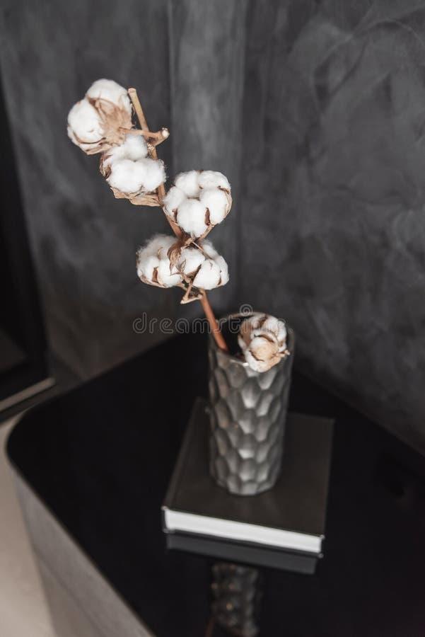 La branche sèche de coton dans le vase en céramique élégant se tient sur le livre noir et la table de chevet moderne de gret le b photos stock