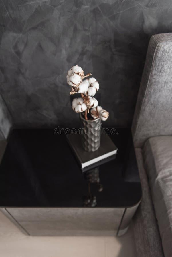 La branche s?che de coton dans le vase en c?ramique ?l?gant se tient sur le livre noir et la table de chevet moderne de gret le b photographie stock libre de droits