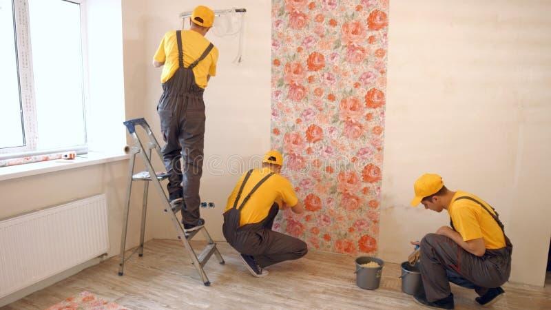La brigada de constructores cuelga el papel pintado en el apartamento imágenes de archivo libres de regalías