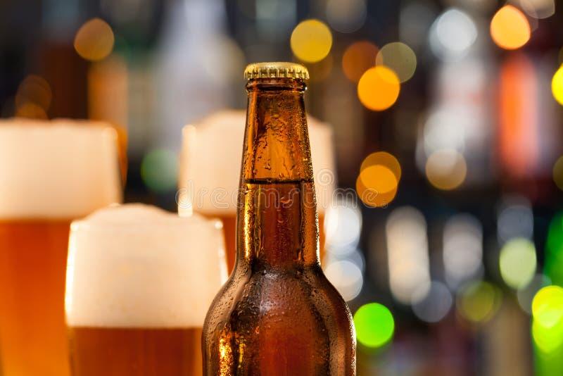 La brocca di birra con la bottiglia è servito sul contatore della barra immagini stock libere da diritti