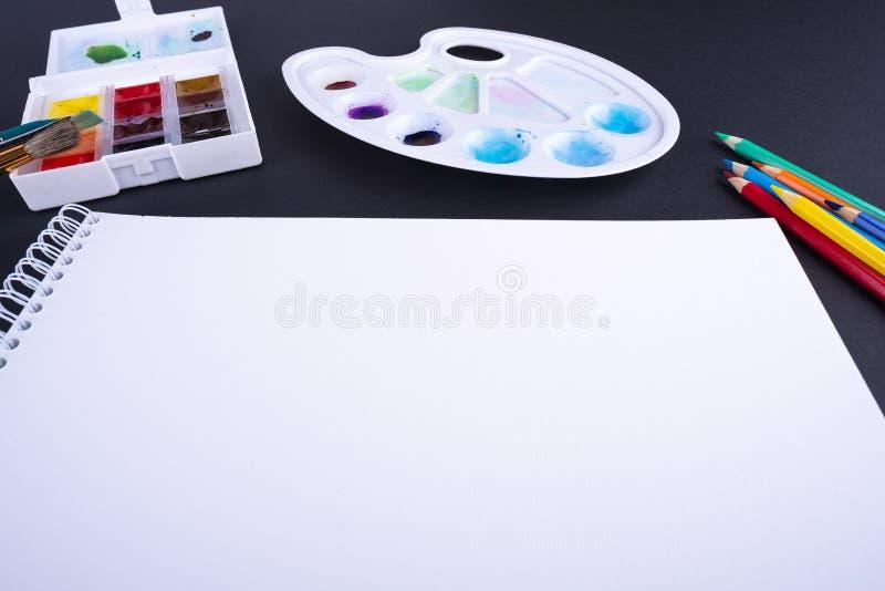 La brocha del lápiz del papel del espacio de trabajo del artista del pintor pinta en el fondo oscuro del ángulo foto de archivo