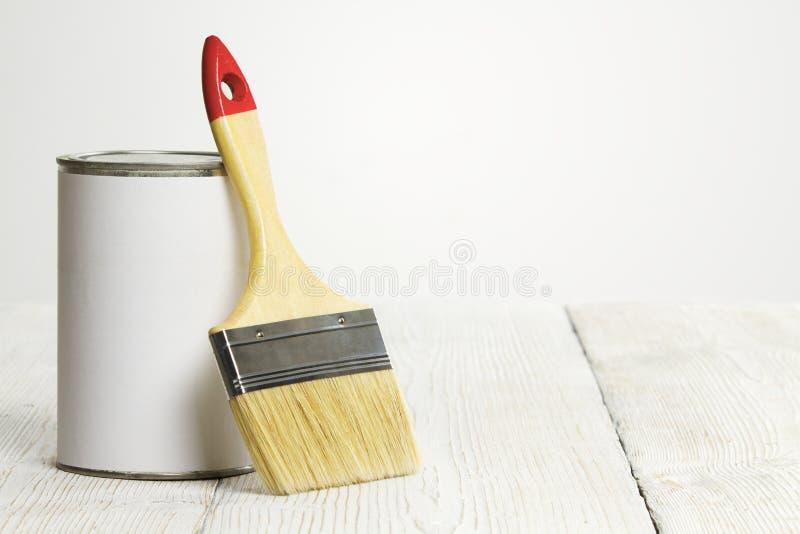 La brocha y puede, brocha y color del blanco en piso de madera imágenes de archivo libres de regalías