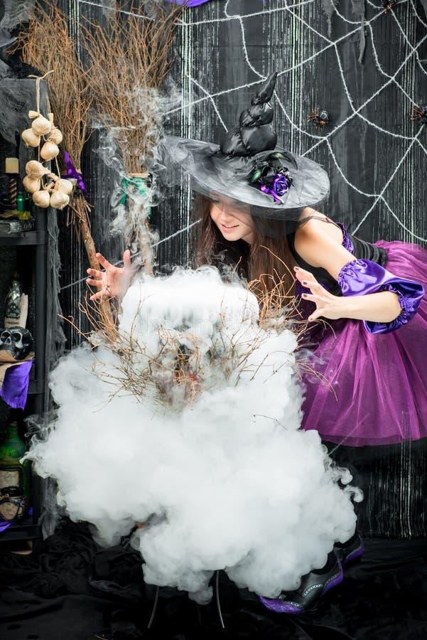 La bruja conjura y cocina una poción de amor fotografía de archivo libre de regalías