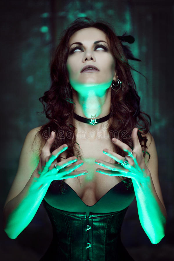 La bruja crea magia Mujer hermosa y atractiva con una luz mística imagenes de archivo