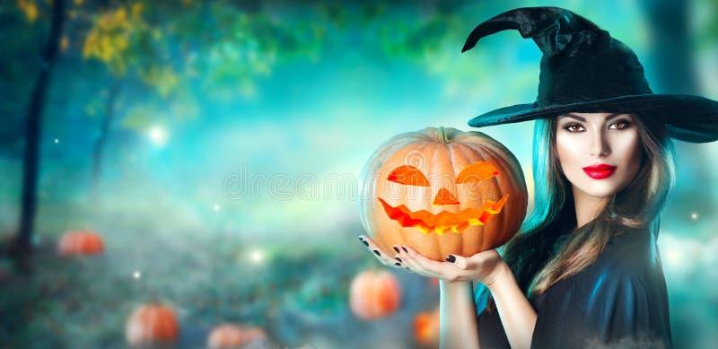 La bruja de Halloween con una calabaza y una magia talladas se enciende en un bosque foto de archivo