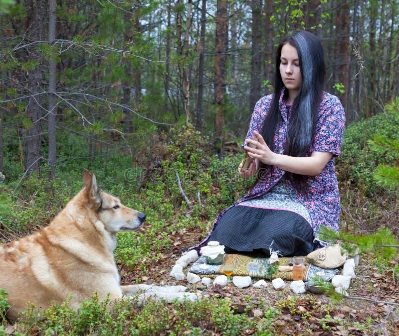 La bruja de la muchacha conjura en el bosque Cerca de un perro enorme foto de archivo libre de regalías