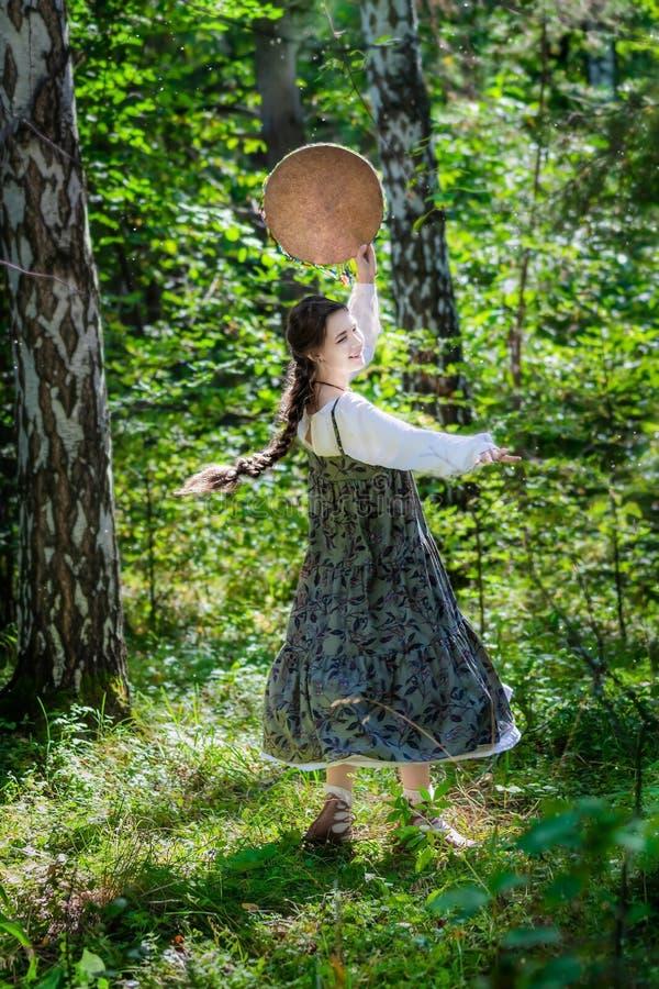 La bruja de la muchacha realiza una danza ritual con una pandereta imagen de archivo