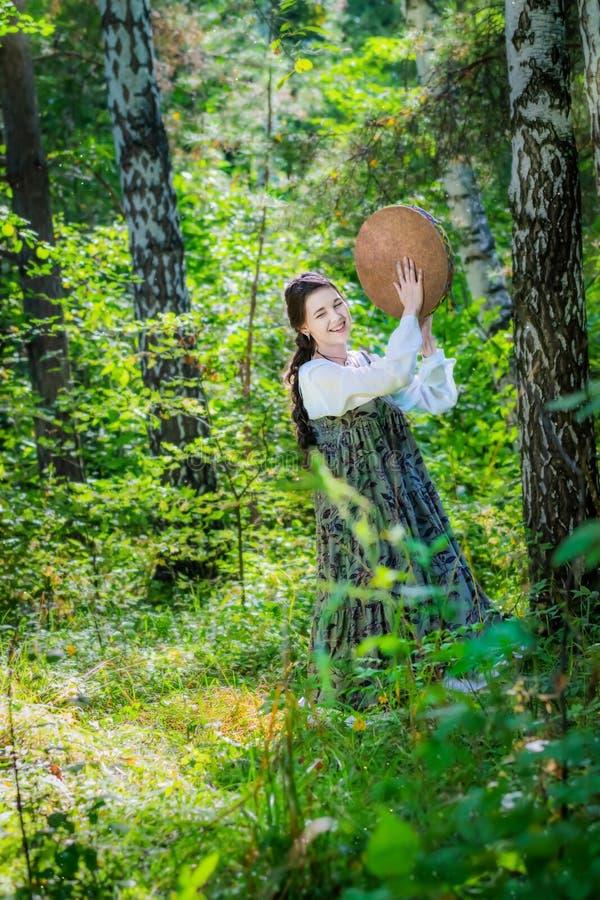 La bruja de la mujer realiza una danza ritual con una pandereta imagenes de archivo
