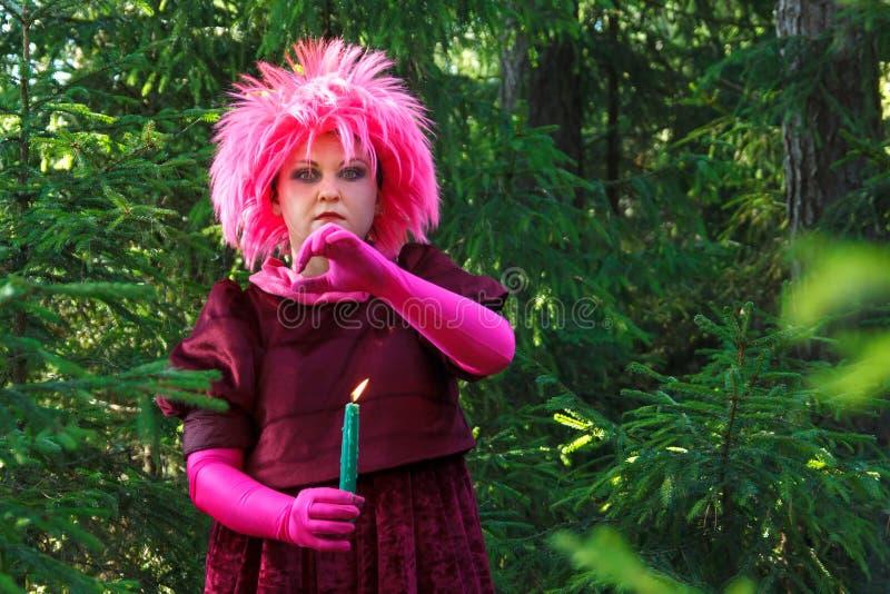 La bruja del bosque en ropa púrpura conjura entre el bosque con las velas Foto vertical imagen de archivo libre de regalías