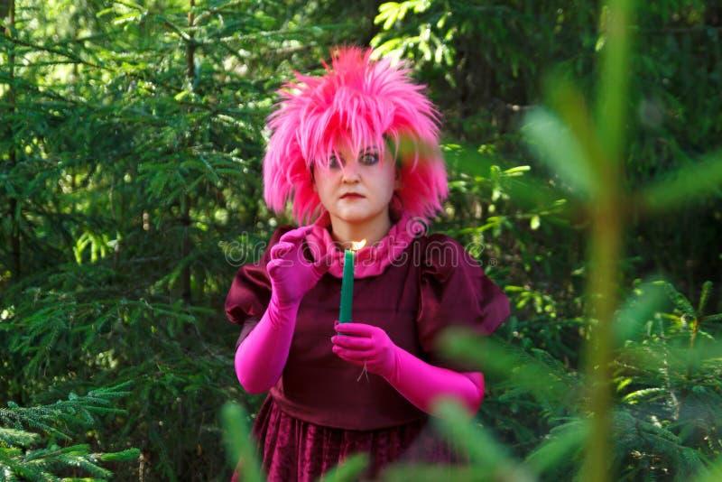 La bruja del bosque en ropa p?rpura conjura entre el bosque con las velas Foto vertical foto de archivo libre de regalías